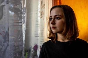 Portrait of a young teenage girl in a room by the window in the evening photo
