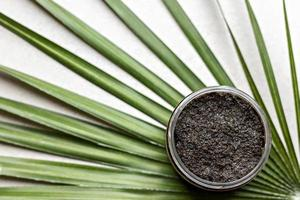 Body scrub made from natural ingredients in a jar on a palm leaf background.Handmade cosmetics. Home spa. photo