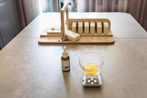 A soap-maker weighs aromatic oils for making cosmetics on a kitchen scale. Home spa. Small business photo