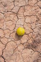 Pelota de tenis amarilla en el suelo del desierto, calentamiento global foto