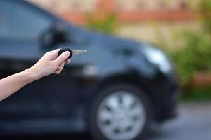 Salesman holding Key of car and car parked  background photo