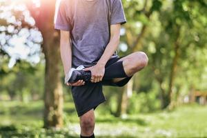 Hombre estirando los músculos de las piernas antes de hacer ejercicio, entrenamiento de atleta joven corredor masculino foto