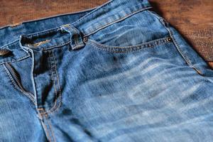 Blue mens jeans denim pants on wooden background. Fashion clothing concept. photo