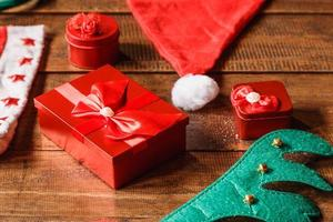 Red gift box and santa hat on wooden background photo