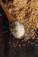 Arroz crudo al vapor y arroz con cáscara sobre fondo de madera foto