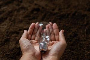 Cerrar mano sujetando la bombilla con suelo, energía segura y concepto de medio ambiente foto