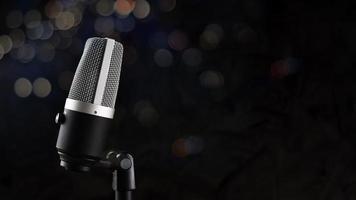 micrófono para grabación de audio o concepto de podcast, micrófono único sobre fondo de sombra oscura y bokeh con espacio de copia foto