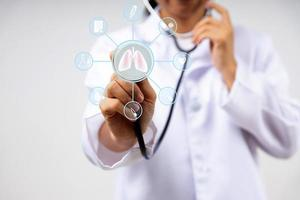 digital screen icon and doctor in uniform use stethoscope to check lung photo