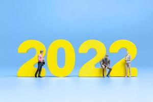 Gente de negocios en miniatura de pie en el número 2022 foto