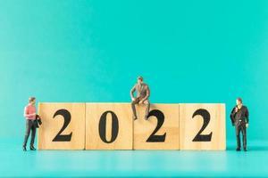 Gente de negocios en miniatura de pie sobre el bloque de madera número 2022 foto