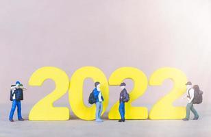 Mochilero de personas en miniatura de pie sobre el número de madera 2022 foto