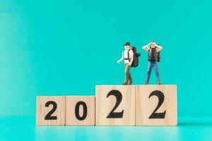 Mochileros en miniatura y turista de pie sobre el bloque de madera número 2022 foto