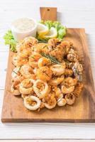 Mariscos fritos de calamar, camarones, mejillones con salsa sobre tabla de madera foto