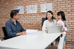 una madre gerente que trabaja y habla con un empleado asiático en el escritorio en una sala de reuniones de una oficina de negocios con paredes de ladrillo naranja mientras su hija entra y sonríe. foto