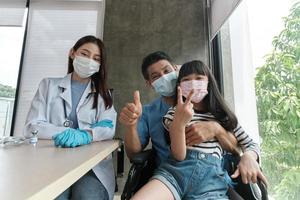 Asian girl and father taking a selfie after vaccinating. photo