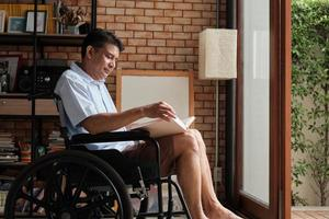 Retired man is reading a book in a wheelchair at home. photo