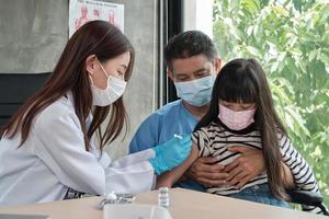 Doctora vacunando a una niña asiática en la clínica de pediatría. foto