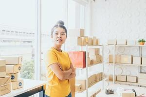 Asian woman business owner working at home with packing box on the workplace - online shopping SME entrepreneur or freelance working concept photo
