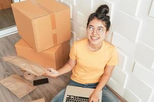 Young Asian business start up online seller owner using computer for checking the customer orders from email or website and preparing packages  - online shopping or sell online concept photo