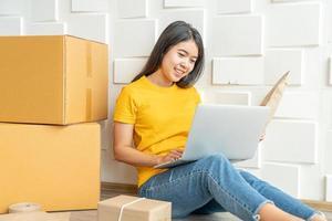 Joven empresa asiática inicia el propietario del vendedor en línea usando la computadora para verificar los pedidos de los clientes desde el correo electrónico o el sitio web y preparar paquetes: compras en línea o concepto de venta en línea foto