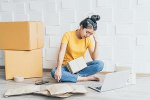 Joven asiática que se siente estresada o deprimida frente a su computadora portátil - concepto de venta en línea foto