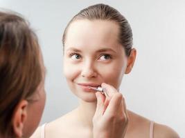 Beautician treats lips, facial treatment photo