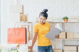 Joven asiática comprobando los productos en el estante de existencias en el almacén - concepto de compra o venta en línea en línea foto