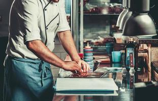 Busy chef at work in the restaurant kitchen photo