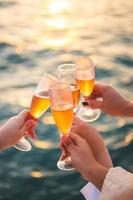 Hand holding a glass drinking wine on Sunset sea background. photo