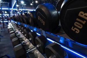 mancuernas colocadas en estantes en el gimnasio para hacer ejercicio. foto
