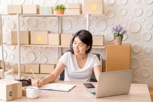Joven mujer asiática puesta en marcha de una pequeña empresa que trabaja con una tableta digital en el lugar de trabajo: venta en línea, comercio electrónico, concepto de envío foto