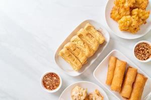 Fried taro, corn, tofu, and spring rolls with sauce - vegan and vegetarian food style photo
