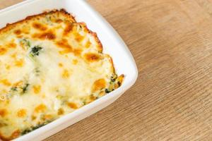 Baked spinach lasagna with cheese in white plate photo