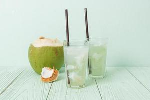 Coconut water or coconut juice in glass with ice cubes photo
