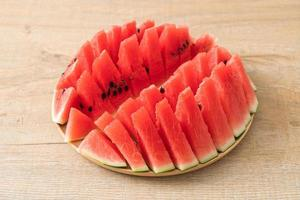 Fresh watermelon sliced on wooden plate photo