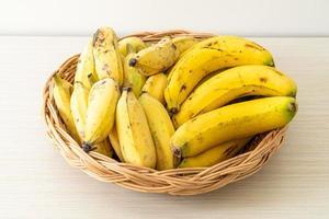 Plátanos amarillos frescos en la canasta sobre la mesa foto