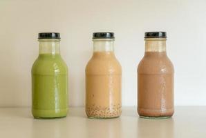 Té verde matcha con leche, té de chocolate y leche con gelatina de pudín en botella de vidrio sobre la mesa foto