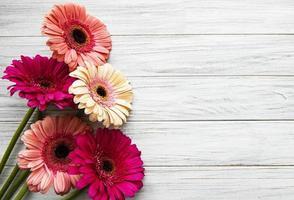 flores de gerbera brillante sobre un fondo de madera blanca. foto