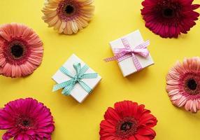 flores de gerbera y cajas de regalo en un amarillo foto