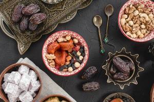 Ramadan juicy dates dried fruits nuts lukum black background. High quality beautiful photo concept
