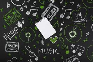 Pizarra de bloc de notas en blanco espiral con notas musicales dibujadas, cintas de cassette, discos compactos. concepto de foto hermosa de alta calidad