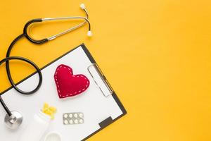 Stethoscope stitched heart medicine falling from bottles blister packed medicine with clipboard yellow table. High quality beautiful photo concept