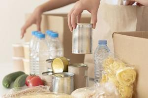 Volunteers putting canned food donation box. High quality beautiful photo concept