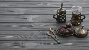 Traditional turkish arabic tea glasses dried dates with spoons wooden table. High quality beautiful photo concept