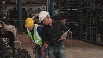propriétaire caucasien et travailleur asiatique. deux hommes vérifiant les pièces du moteur dans un entrepôt. tous deux portant un casque pendant le temps de travail, la plupart des produits sont des machines de l'industrie automobile. video
