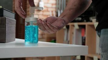 Close-up shot, Casual man is pressing a bottle of alcohol gel, hand sanitizer for health hygiene, and to prevent disease and bacteria such as coronavirus Covid-19while working at the home office. video