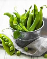 Fresh green peas in a small metal bucket on old wooden background photo