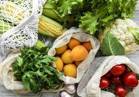 Fresh fruits and vegetables in eco cotton bag photo