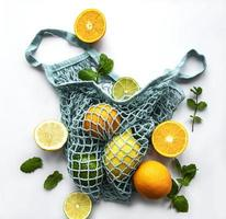 Ripe whole citrus fruits in string bag on white background photo