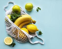 jugosos cítricos maduros y plátanos en una bolsa de compras ecológica foto